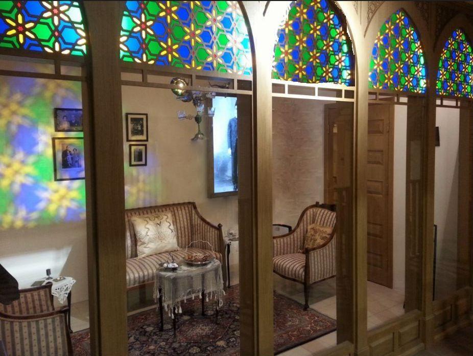 חדר מלבני עם דלת עץ מפוארת, מרוהט בריהוט ויקטוריאני  עם שטיח פרסי, שולחן כיבוד עם מפת תחרה ותמונות על הקיר. חזית החדר מורכבת מקשתות עץ מחודדות שזוגגו בקשתות בויטראז' צבעוני בדגמים פרחיים וגיאומטריים. צבעי הויטראז' משתקפים על הקיר הלבן שממול ומשרים בסלון אווירה נעימה.