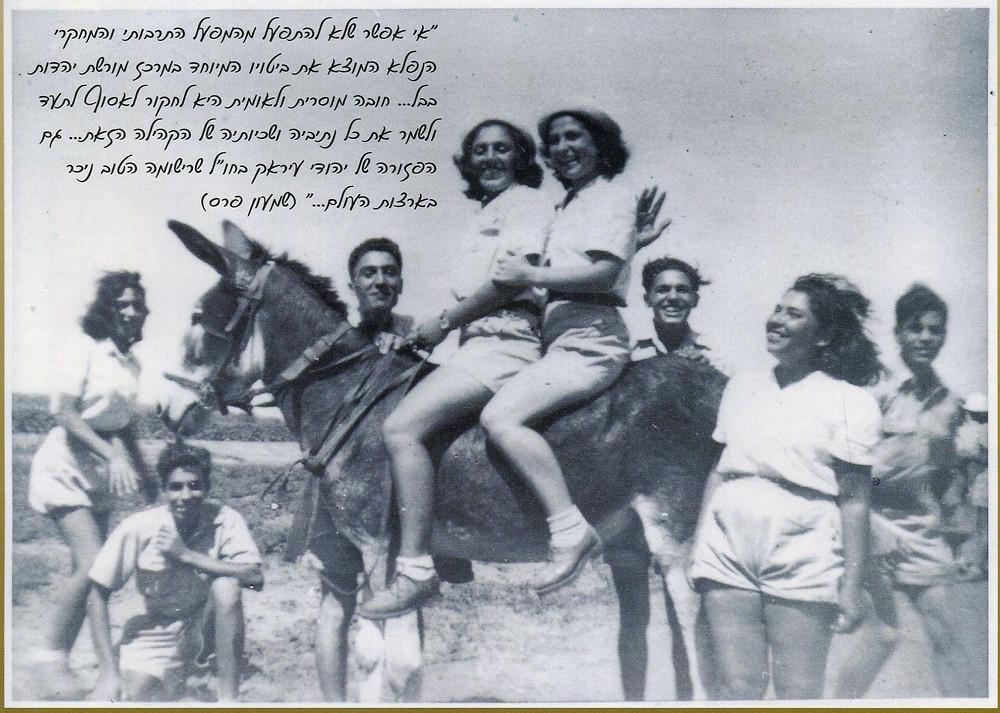 חבר'ה צעירים עומדים בשטח פתוח, לבושים במכנסיים קצרים ובחולצת צווארון מכופתרת, במרכז התמונה עומד חמור ועל גבו שתי פעילות.