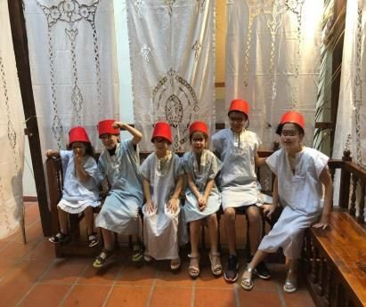 Inside a restored sukkah from Iraq, a group of children dressed in white galabiyas and red men tarboosh hats is sitting on a wooden bench. White sheets decorated with lace serve as the walls of the sukkah.