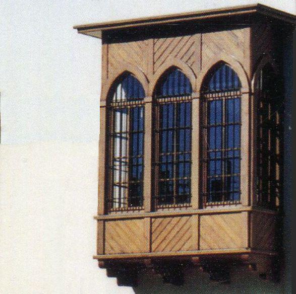 מקיר החזית בולטת מרפסת עשוייה עץ, היא מוקפת בקשתות מחודדות שזוגגו בזכוכית. המרפסת נשענת על ארבע תמיכות עץ ומעליה בולט גגון עץ.