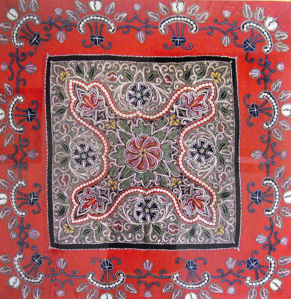 בד בצורת מרובע, שבמרכזו מרובע קטן יותר. המרובע החיצוני ברקע אדום ומסביב רקומות צורות של עלים וניצנים. הריבוע הפנימי בצבע ירוק עם רקמה צפופה יותר של פרחים, עלים וסלסולים.
