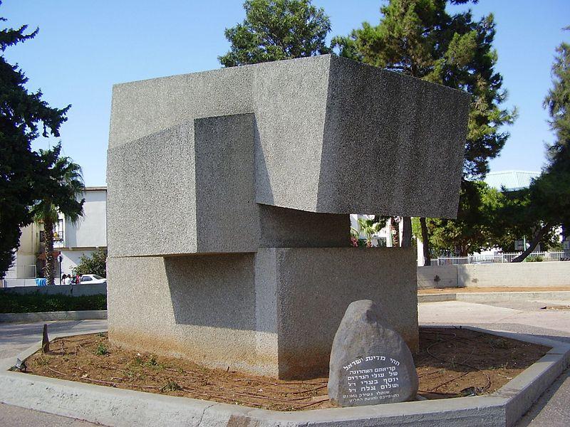 ברחבה שלפני בניין מרכז מורשת יהדות בבל, מעל גינה מוגבהת, ניצבת אנדרטה המזכירה קוביות המונחות האחת בתוך ומעל השנייה.