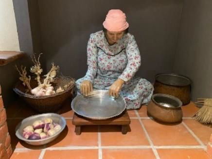 A woman is sitting on the floor, wearing a floral house robe and a headscarf. She is surrounded by pots and in prepare herself for cutting onions for cooking the meal.