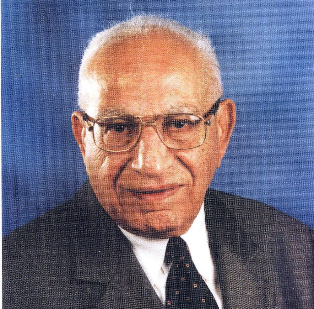 A man in his middle years, wearing eyeglasses, has a short and white hair, wearing a white shirt with a dark tie and a black jacket