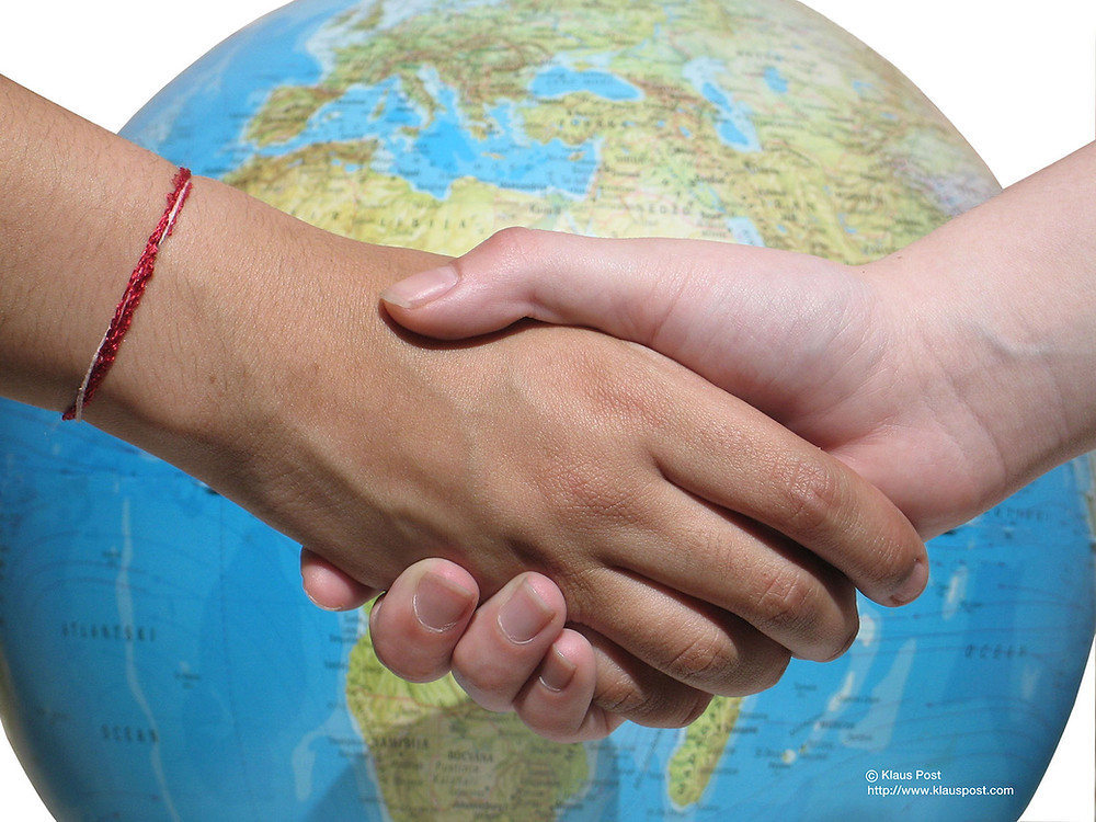 Two hands clasp in front of a world globe.