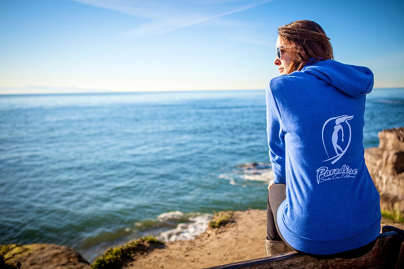 Paradise surfer girl checking the surf at Pleasure Point wearing a classic Paradise hooded sweatshirt