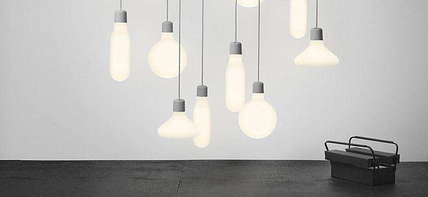 Lampade pendendi con cassetta degli attrezzi, su suolo scuro e parete grigia