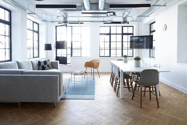 Salone illuminato a giorno con tavolo da pranzo e divano, arredamento con mobili di design