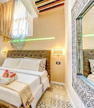 Stanza di un B&B con letto, specchio a muro e illuminazione LED