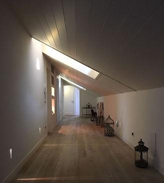 Corridoio interno di una mansarda con pavimento e soffitto in legno