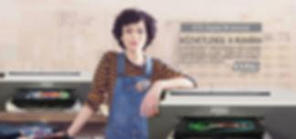 Barna hajó lány egy pólónyomtató műhelyben állva pólónyomtató gépek mellett
