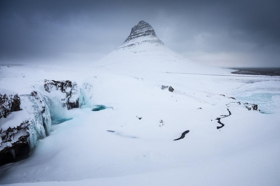 Mount Kirkjufell in Iceland during wintertime and frosen waterfall