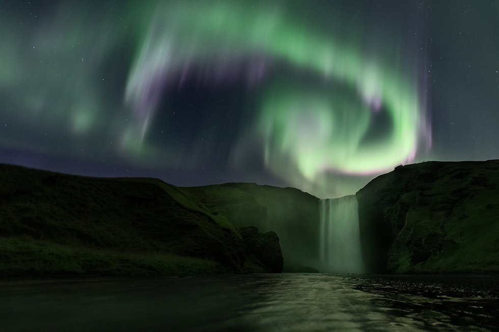Dancing northen lights over Skógafoss in Iceland