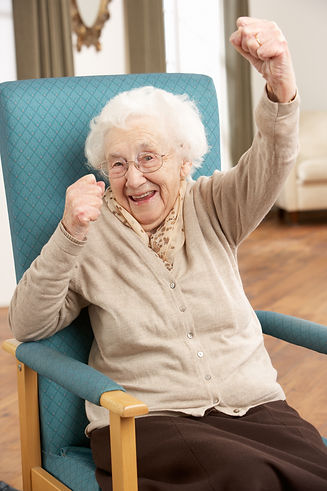 Photo of an elderly woman sitting in a chair with her fist in the air.