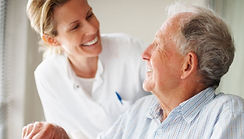 Photo of elderly man smiling at a care assistant
