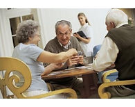 Photo of a group of happy seniors at a table playing cards.