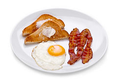 A breakfast plate with toast, fried egg and three pieces of bacon