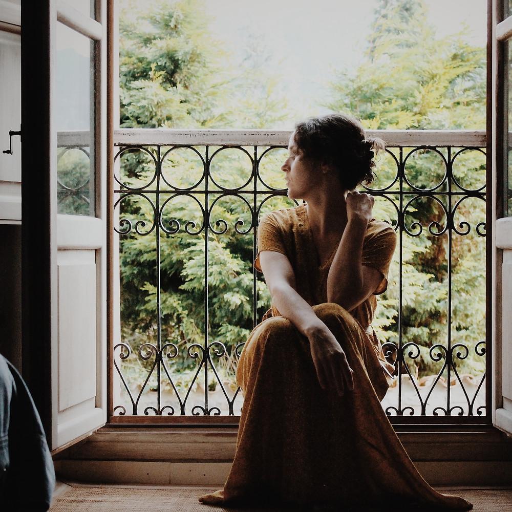 Woman sitting in front of an open window