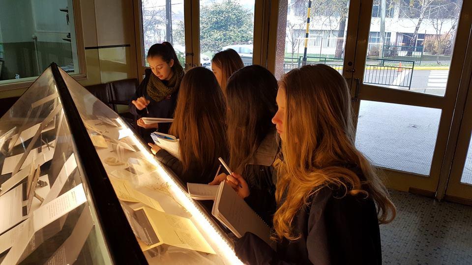 Estudiantes observan y toman apuntes sobre la esposición