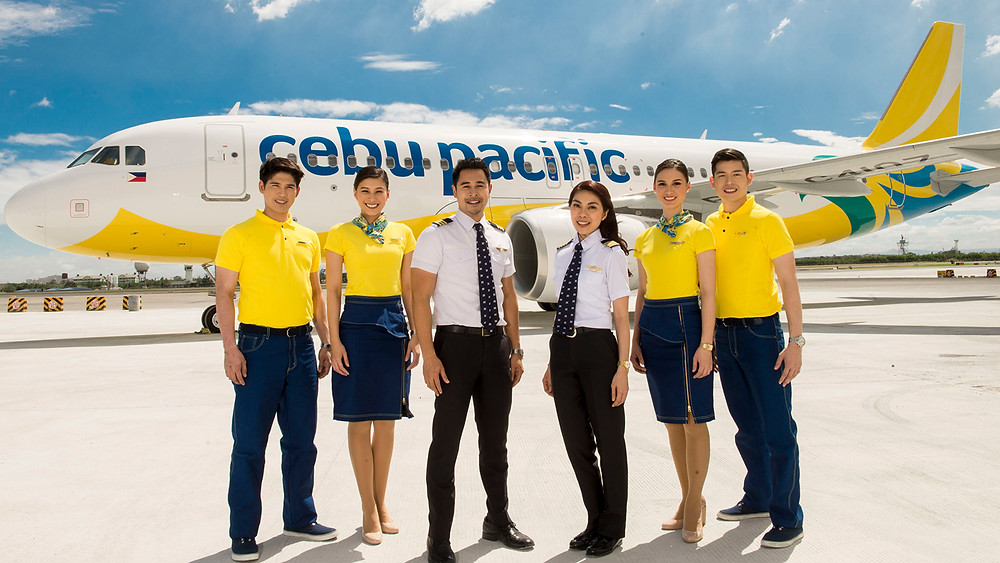Cebu Pacific Staff wearing yellow Uniform in front of airplane.