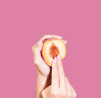 Canva - Woman holding a slice of peach.j