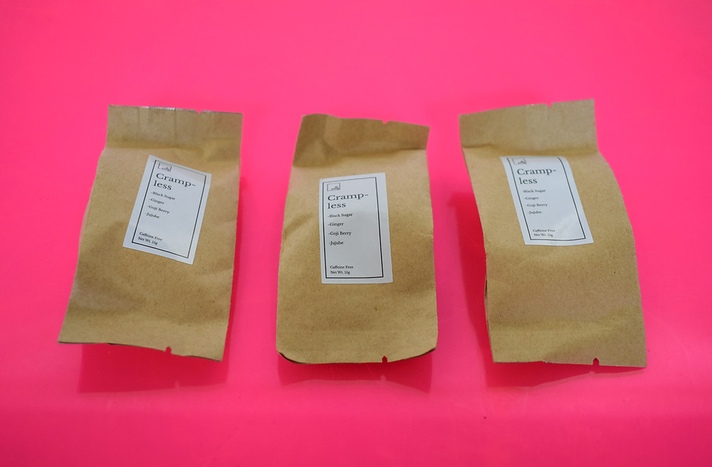 This is a photo of Dr. Yang Wellness tea in it's individual packaging on a pink background.