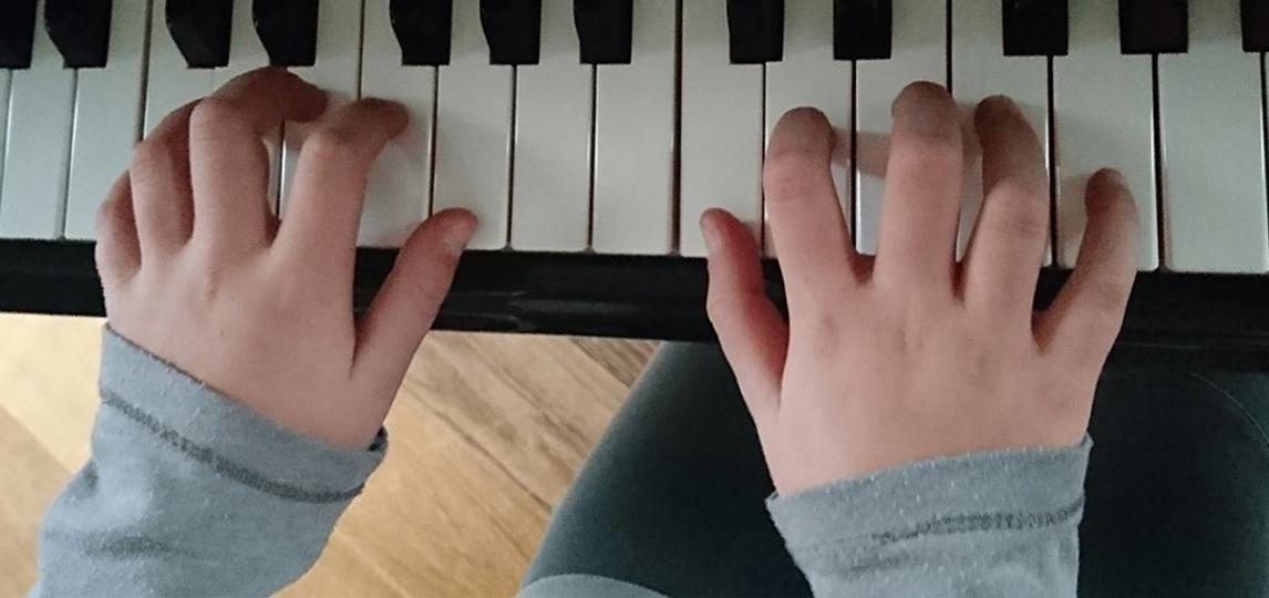 Klavier-Tastatur mit Schüler-Händen
