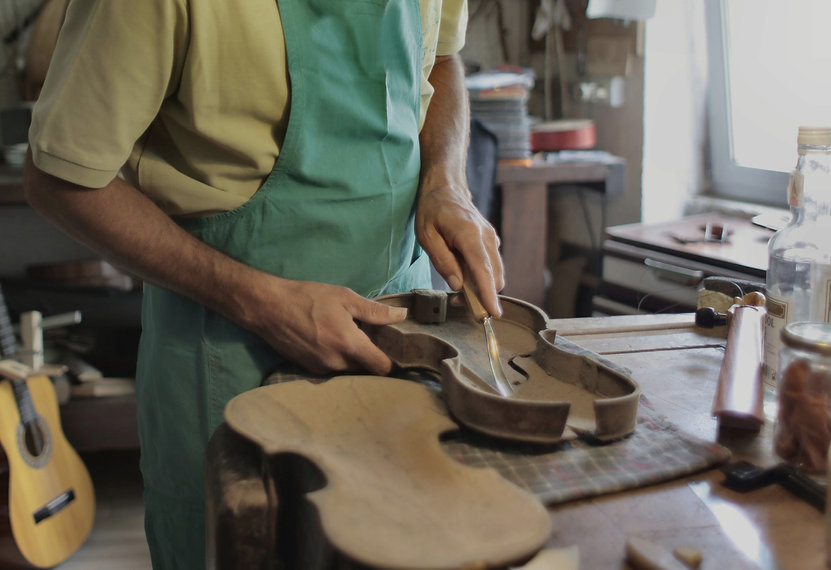 crop-male-artisan-cutting-violin-from-tr