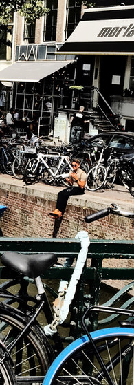 boy sitting at canal amsterdam centrum keizersgracht morlang boats bicycles bridge iphoneonly
