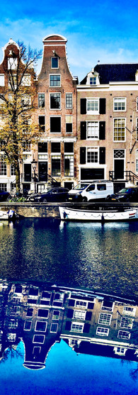 canal houses at keizersgracht with reflection on roof of blue car