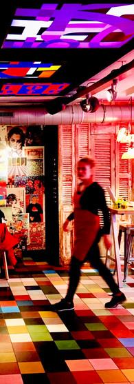 inside colorful happyhappyjoyjoy ceintuurbaan de pijp with waitress walking into the photo