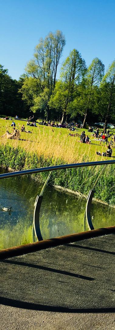 brug in rembrandtpark amsterdam west op zomerdag met schaduw op weg en zonnende mensen op achtergrond