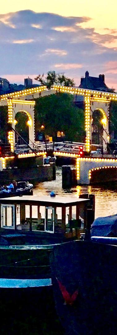 magere brug bij zomeravond mooi verlicht amsterdam amstel met boot op voorgrond