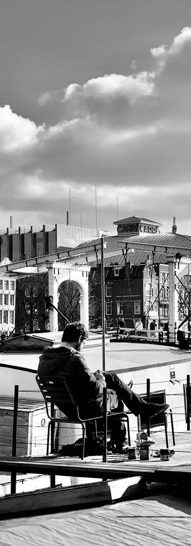 man alleen zit rustig te lezen op dak woonboot amstel met magere brug en carré op de achtergrond amsterdam
