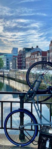 fiets op zijkant tegen reling van brug bij koningsplein amsterdam singel met bloemenmarkt op achtergrond