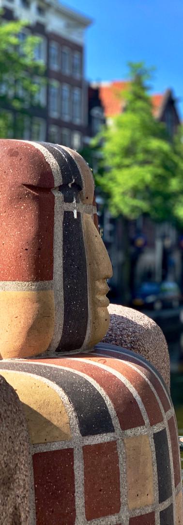 amsterdamse school boeddha standbeeld bij de wallen met oude kerk op de achtergrond