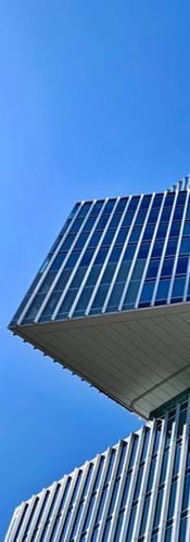 nhow amsterdam rai hotel with airplane crossing the blue sky
