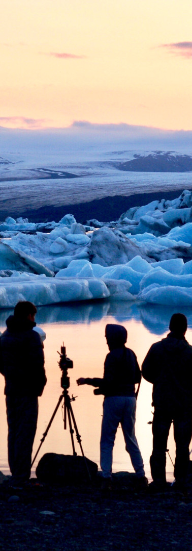 jokulsarlon glacier on summer evening with photographers' silhouettes in front