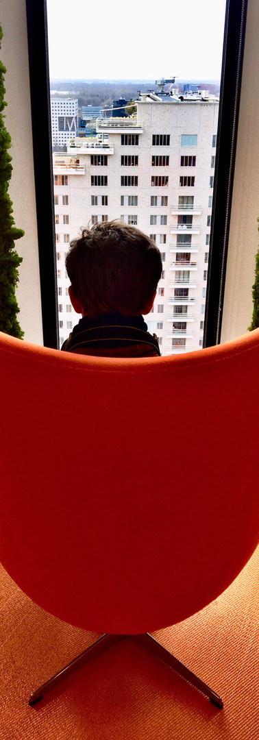 boy sitting in orange easy chair facing to the other side and looking out of the window from symphony office building amsterdam zuidas