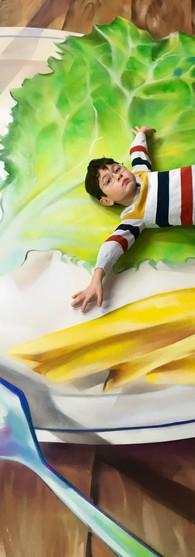 jongen ligt op bord met sla tomaat en frietjes in museum illusions wallen amsterdam