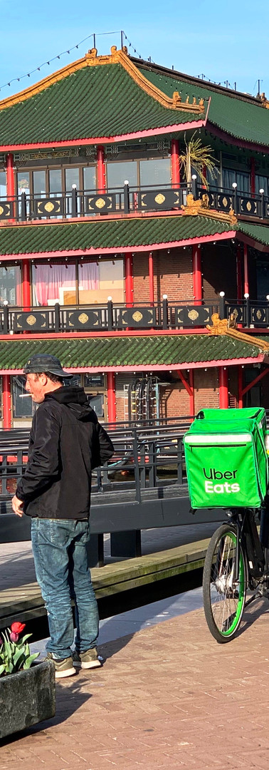 bezorger uber eats pauzeert met sigaret naast zijn fiets op oosterdokskade in de ochtend met sea palace op achtergrond