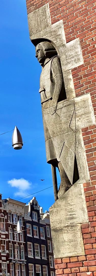 beeldhouwwerk ingehouwen in de wand van de beurs van berlage amsterdam met damrak huizen op achtergrond
