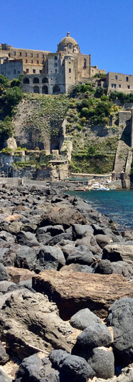 castello aragonese ischia grey basalt rocks blue water castle on rock capri in the distance italy sunshine