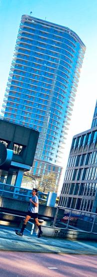 man is aan het hardlopen in omval amsterdam met amsteltoren op achtergrond op zonnige zondagochtend amsterdam