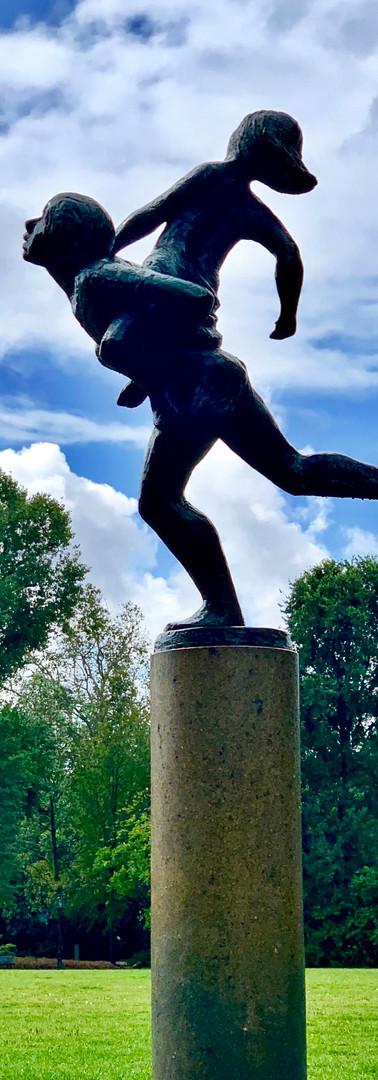 jongen met meisje op de rug rennend als standbeeld in oosterpark amsterdam tegen achtergrond van gras en bos en lucht