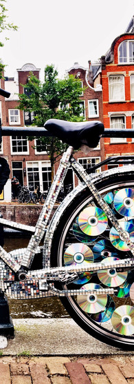 bike full with wheels full of cds at canal amsterdam iphoneonly
