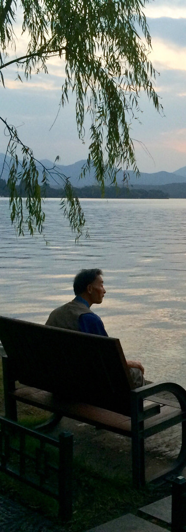 time for reflection westlake hangzhou china man alone at lake evening dusk water serenity