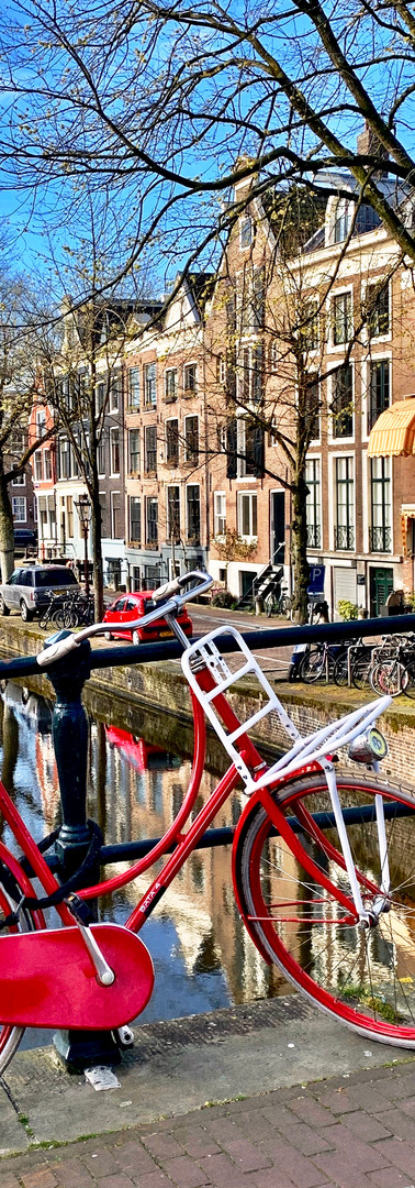 red and white bicycle on reguliersgracht amsterdam on sunny spring morning with backdrop of canal houses