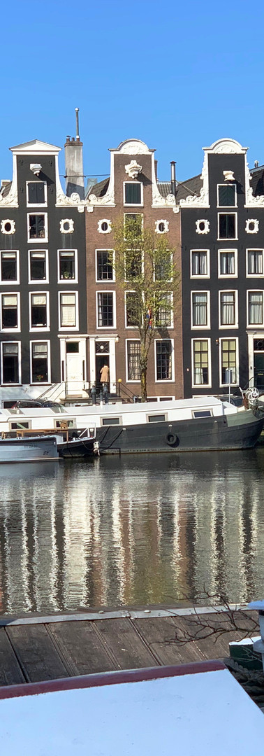 young man on houseboat with canal houses in background on amstel river amsterdam