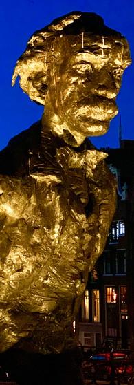 verlicht multatuli standbeeld aan singel amsterdam bij zomeravond met donkerblauwe lucht